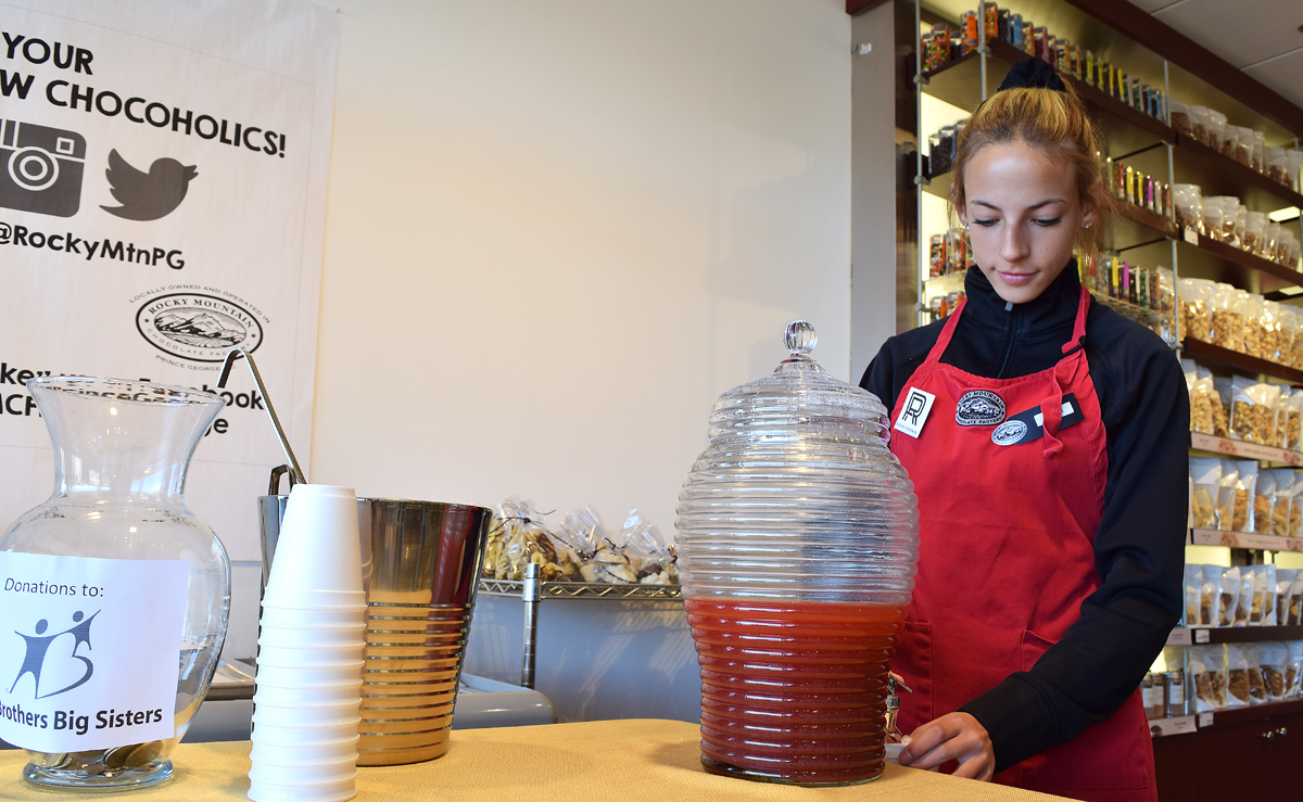 Taylor Malgunas pours a nice cool glass of juice at the Rocky Mountain Chocolate Factory, just one of a couple dozen businesses taking part in the Big Squeeze ... a fundraiser for Big Brothers and Big Sisters in Prince George. Bill Phillips photo