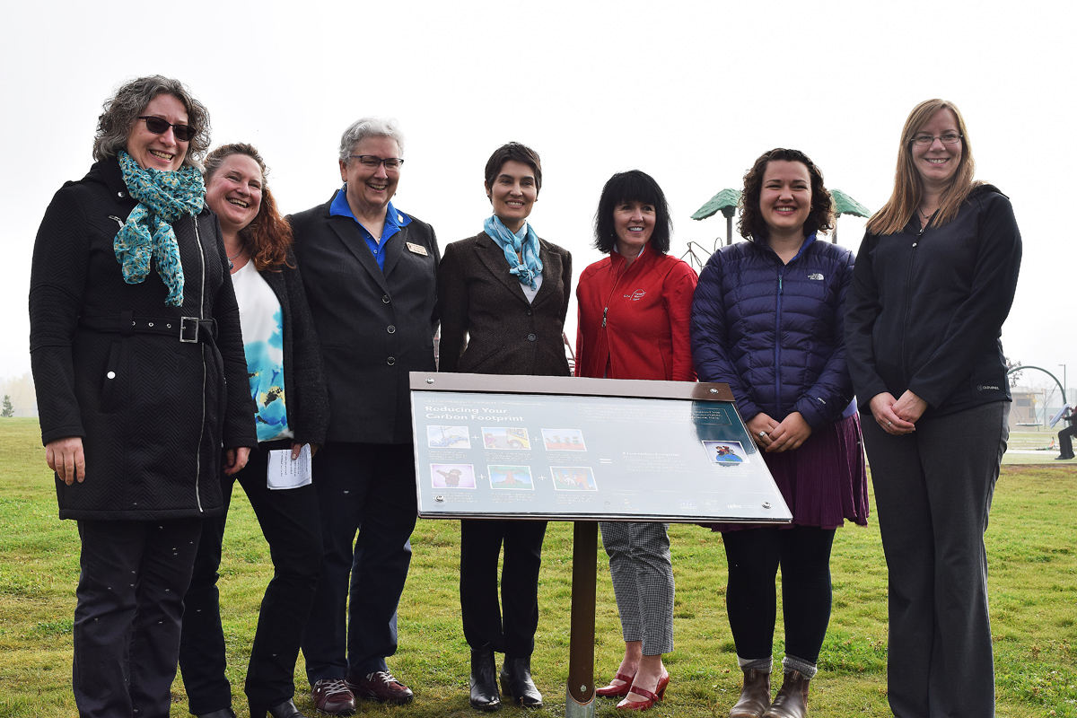 Barbara Otter (left), Chamber of Commerce program manager for the CN Carbon Reduction Project, Sherry MacIntyre of PG AIR, Coun. Susan Scott, Michelle Connolly of the Pacific Institute for Climate Solutions, Lori Needhaw of CN, UNBC student Rachelle Linde, and Chamber of Commerce CEO Erika Ewacha unveil a plaque commemorating the CN Carbon Reduction Project. Bill Phillips photo