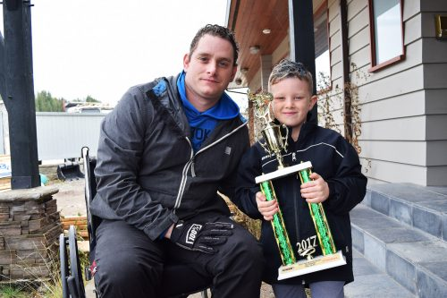 Trevor and Lyndon Patenaude show off one of the trophies Lyndon won this year in motocross. Bill Phillips photo