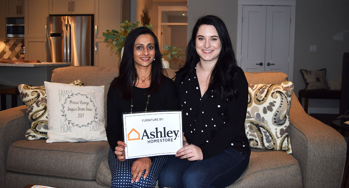 Sangeeta Kandola Low of Ashley Homestore and Sanja Knezevic of Prince George Hospice sitting on a wonderful sofa in the Hospice House Dream Home that you could take home. Bill Phillips photo