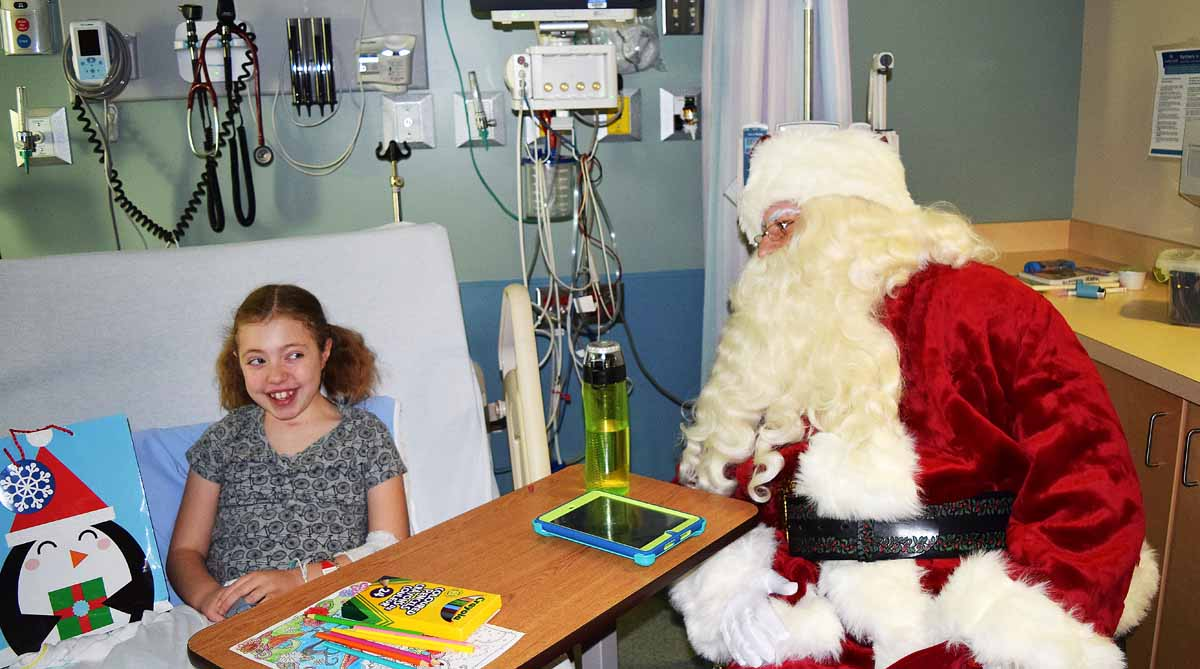 "Laurel Taylor, 11, gets a visit from Santa Claus in the pediatrics ward at the University Hospital of Northern B.C. Wednesday. ""He's funny,"" Laurel said of the Big Guy. Bill Phillips photo"