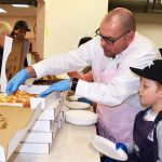 Lyndon Patenaude helps Cariboo-Prince George MP Todd Doherty serve pizza at St. Vincent de Paul Thursday. Bill Phillips photo