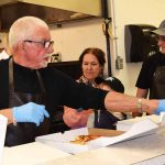 John Brink serves up pizza at St. Vincent de Paul. Bill Phillips photo