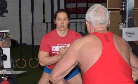 Tara Bogh of XConditioning helps John Brink warm up before a training session. Bill Phillips photo