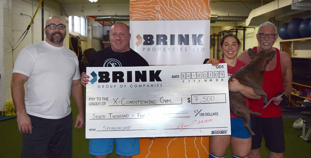 Jay Cook (left), Mike Webber, and Tara Bogh (with Dozer) of XConditioning accept a $7,500 cheque from John Brink. The Brink Group of Companies is the title sponsor of the 2018 Canadian Powerlifters Association Open May 26-27. Bill Phillips photo