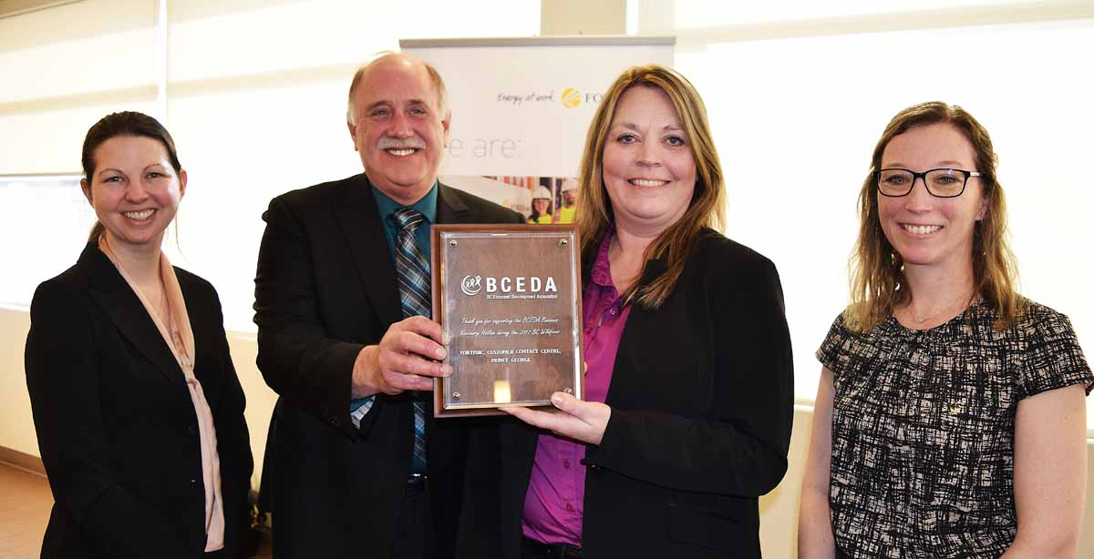 Dale Wheeldon, president and CEO British Columbia Economic Development Association, presents Dawn Mehrer, vice president of customer contact centres, FortisBC with a plaque in recognition of FortisBC's help during last summer's wildfires. Emily Columbo, regional economic development officer for the Cariboo region (left) and Amy Reid, economic development officer with the City of Quesnel look on. Bill Phillips photo