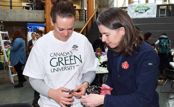 Laura Pyke (left) and Belinda Larisch reclaim old innner tubes, turning them into watch straps and bracelets during Green Day at UNBC. Bill Phillips photo