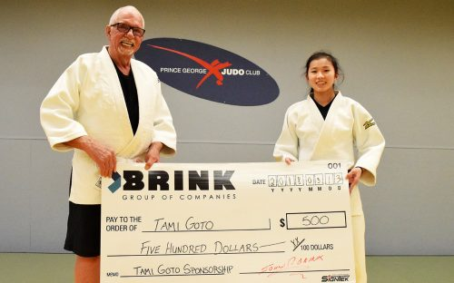 John Brink, of the Brink Group of Companies, presents judokan Tami Goto with a sponsorship cheque of $500.