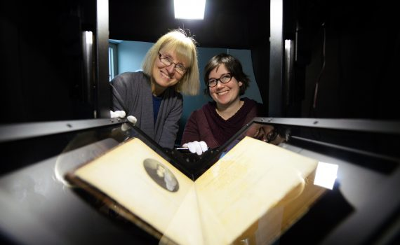 Head of Archives & Special Collections Ramona Rose (left) and Archivist/Librarian Kim Stathers pose with Alexander Mackenzie's 1801 book Voyages from Montreal in scanning machine. The book is one of many digitized thanks to a donation to the Northern Leadership Campaign. UNBC photo