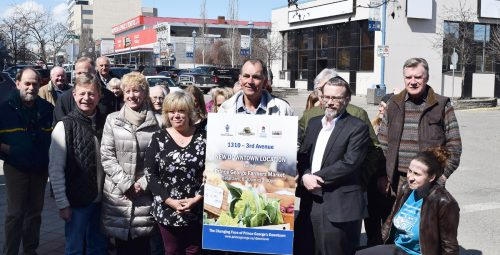 Prince George Farmers Market president Phil Myatovic (holding sign), Community Arts Council executive director Sean Farrell (right), Coun. Terri McConnachie and Colleen Van Mook of Downtown Prince George are flanked by other members of council, the arts community, and farmers market as they announce a new partnership. Bill Phillips photo