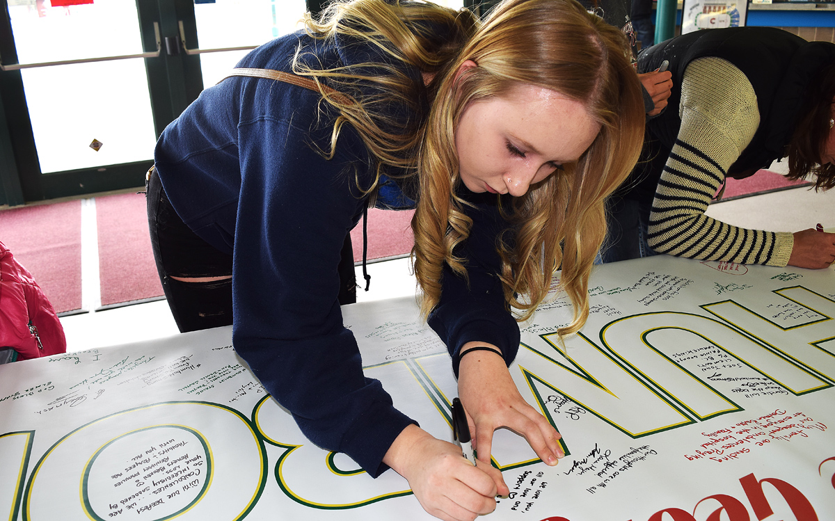 Shay Glaicar signs a banner for Humbolt, Saskatchewan at CN Centre Tuesday. Bill Phillips photo