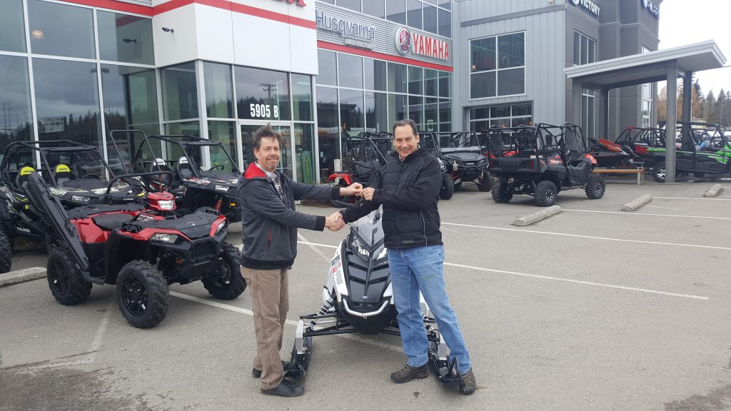 James Klein, grinning from ear to ear, the winner of the 2018 Polaris Indy snowmobile. The raffle was a fundraiser for the PG Snowmobile Club. Handing over the keys at Cycle North Saturday is Marty Anderson, vice-president of the Prince George Snowmobile Club. Photo submitted