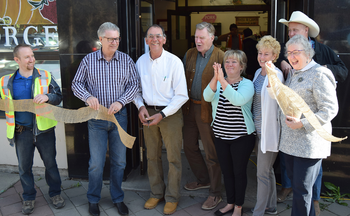 Phil Myatovic cuts the burlap to officially open the Prince George Farmer's Market at its new location at Third Avenue and Quebec Street. Helping out are Mayor Lyn Hall, Coun. Terri McConnachie, Susan Scott and Albert Koehler; Colleen van Mook of Downtown Prince George and Martin Krell of the Farmer's Market. Bill Phillips photo
