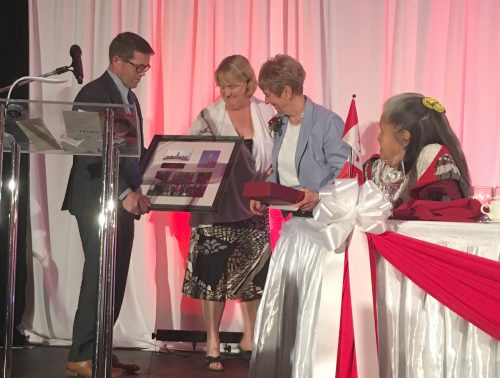 MP Bob Zimmer and MP Cathy McLeod present Nancy Greene Raine with the flag that flew over the Peace Tower on her last day as a Senator
