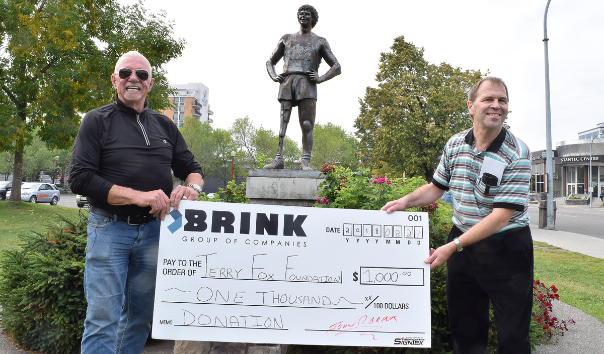 John Brink of the Brink Group presents Jim Terrion with a cheque for $1,000, bringing Terrion's fundraising efforts for the Terry Fox Foundation to just over $720,000. Bill Phillips photo