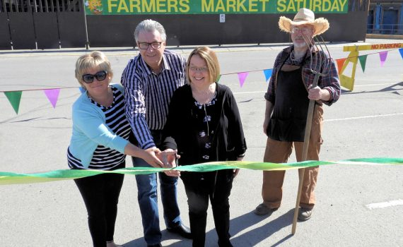 Coun. Terri McConnachie (left), Mayor Lyn Hall, and Prince George-Valemount MLA Shirley Bond cut the ribbon to officially open the Wilson Square Farmer's Market at Pine Centre Mall Saturday. Photo Submitted