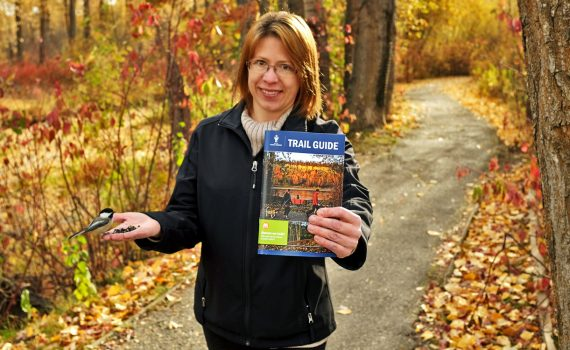 Community Coordinator Marta Gregor holds aloft the latest edition of the Trail Guide and a wee chickadee she met along one of the many trails of Cottonwood Island Nature Park. City of Prince George photo
