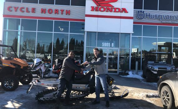 Prince George Snowmobile Club vice-president Marty Anderson hands the key of a 2018 Polaris RMK 800 snowmobile over to Peter DeSilva. The snowmobile was the grand prize in the club's 2018/19 raffle.
