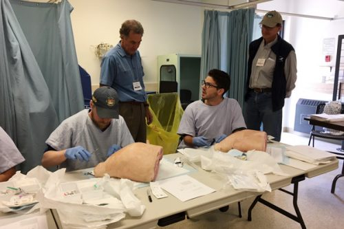 Dr. Stuart Johnston teaching tendon repair and skin flaps (using pigs' legs) to Dr. Kalun Boudreau, Fort St. John and James Wilkie, Resident physician, Fort St. John. Dr. Charles Helm, Chief of Staff Tumbler Ridge, observing. Northern Health photo