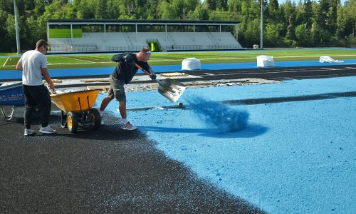 A contracted worker lays rubber down as part of the installation of the new track at Masich Place Stadium. City of Prince George photo