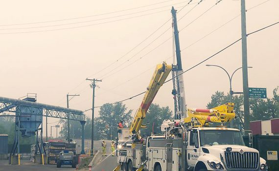 A conveyor pipe over River Road between two Brink Forest Products buildings gets repaired.