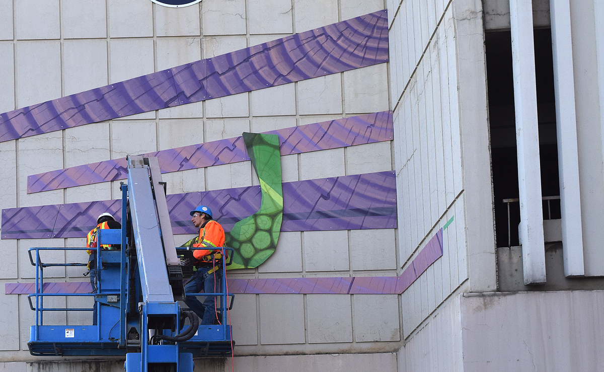 Crews install a mural on the Plaza parkade downtown. Bill Phillips photo
