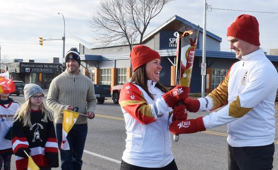 Alyson Gourley-Cramer passes the Roly McLenahan Canada Games Torch to Joel McKay during the torch run for the 2019 Canada Winter Games, which will be held in Red Deer. Bill Phillips photo