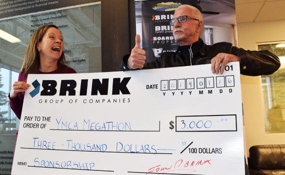 YMCA of Northern BC CEO Amanda Alexander is all smiles as John Brink, of the Brink Group of Companies, signs on a major sponsor for the YMCA Megathon with a $3,000 donation. Bill Phillips photo